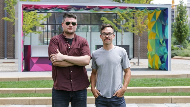 "Project One digital design/fabrication studio partners, Kyle Perry, left, and Adam Buente, right, stand in front of their newest installation, ""Conveyance"", a book share station adjacent to The Alexander hotel in downtown Indianapolis on Tuesday, July 26, 2017."