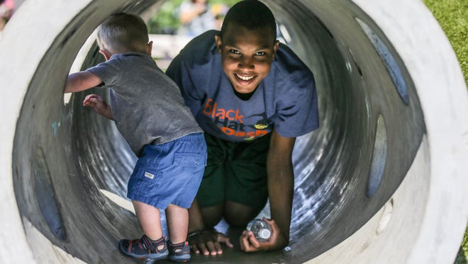 Finnegan Griggs, left, and Harrison Evans, right, play in a tube during the Tarkington Park Community Celebration in Indianapolis on Saturday, July 29, 2017.