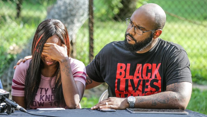 Erica Bailey, the daughter of Aaron Bailey who was shot and killed by IMPD officers is comforted during a press conference by Founder and President of Don't Sleep, Dominic Dorsey near the site of Bailey's shooting, Thursday, August 10, 2017. Bailey, an unarmed African American man drove away from a traffic stop and was shot four times through the back of his vehicle by IMPD officers after a short chase which ended in a crash on June 29, 2017.