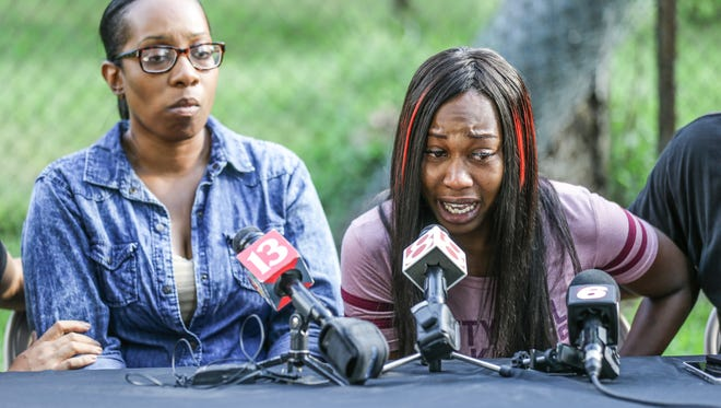Relatives of Aaron Bailey who was shot by IMPD officers, Kimberly Brown, left, and Erica Bailey, right, give an emotional press conference  near the site of his shooting, Thursday August 10, 2017. Bailey, an unarmed African American man drove away from a traffic stop and was shot four times through the back of his vehicle by IMPD officers after a short chase which ended in a crash on June 29, 2017.