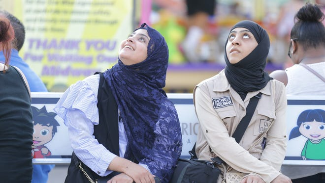Two women watch the Speed ride fly overhead on the last day of the Indiana State Fair in Indianapolis on Sunday, August 20, 2017.