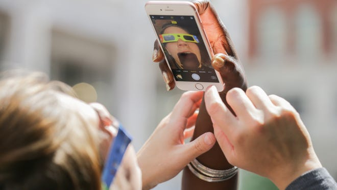 Tiffany Eubanks, left, and Angela Parker, right, take selfies and eclipse photos just off  Monument Circle in Indianapolis on Monday, August 21, 2017.
