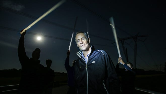 Indy Star Reporter Will Higgins astounds among a group holding florescent light bulbs above their heads while standing on the Electric Bridge causing them to illuminate on Tuesday, Sept. 5, 2017.  Stories of the Electric Bridge have circulated amongst Shelbyville Indiana's teenagers since the 1970's.