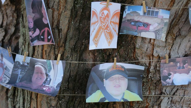 Photos of  Zane Davidson hang on a tree during a ring the bell party celebrating his defeat of childhood cancer at his family home in Morgantown Ind. on Saturday, Sept. 30, 2017. Zane, who lives in Johnson County was diagnosed with acute lymphoblastic leukemia in 2014.