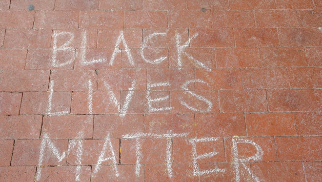 Black lives matter is scrawled on the ground in chalk during an action to bring awareness to Bailey's death organized by DON'T SLEEP, Indy10 Black Lives Matter and others at the City-County Building in Indianapolis on Sunday, Oct. 29, 2017. Aaron Bailey was unarmed when he was shot and killed by IMPD officers.