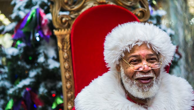 "December 20, 2017 - Raymond Conley, 65, converses with Ivery Williams, 8, during his visit to Southland Mall on Wednesday. Conley, who works for Cherry Hill Photo, has been portraying Santa Claus at the mall for seven years. ""I'm Santa Claus – the only one,"" Conley said. ""I have fun with it. Santa loves the kids."""
