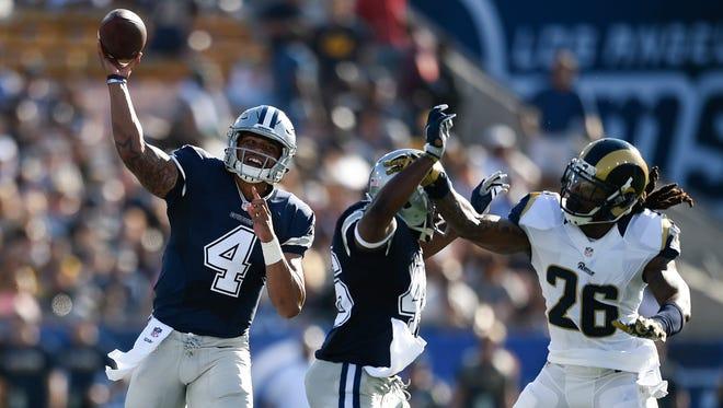 Dallas Cowboys quarterback Dak Prescott (4) throws the ball against the Los Angeles Rams during the first quarter at Los Angeles Memorial Coliseum.