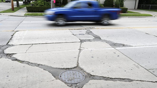 A truck drives past a patched up section of Webster Avenue in Green Bay.