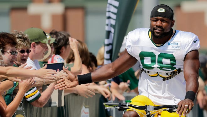 Green Bay Packers running back Ty Montgomery (88) high fives fans on his way to training camp practice on Tuesday, August 8, 2017, at Ray Nitschke Field.