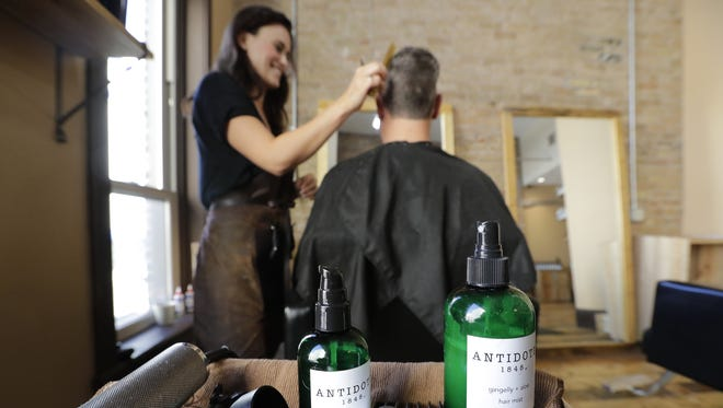 Abigail Kuehl, a co-owner of Bold Salon in Appleton, uses her new Antidote 1848 hair and beard oil and hair mist while giving a haircut to Andy Tillman of Appleton.