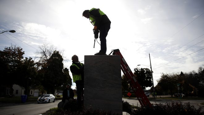 """Alex Schultz, president of Sculpture Valley, helps Steve Maxon, left, of Max-Cast Inc. drill the holes necessary for the placement of the new """"Spirit of the American Doughboy"""" monument on Monday on Memorial Drive in Appleton."""
