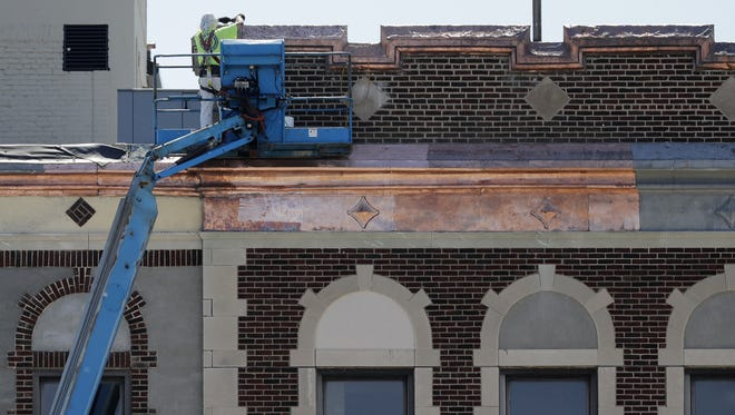 Work was underway on the copper facade accents on the Hotel Northland on Friday. The new owners aim to open the historic downtown Green Bay hotel in October.