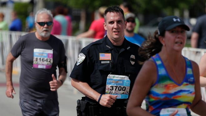 Preston Hajny, an Oconto Falls Police Officer, ran in full uniform in the 2018 Bellin Run 10K on June 9 in Green Bay.  Adam Wesley/USA TODAY NETWORK-Wisconsin