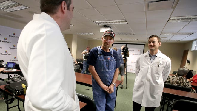 Tim Schroeder, center, speaks Thursday with Dr. Patrick Brennan, left, and Dr. Matthew Butler, right, before a news conference at ThedaCare Regional Medical Center-Neenah about Schroeder's arm reattachment surgery two years ago.