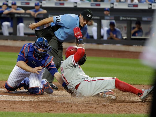 New York Mets catcher Devin Mesoraco, left, tags out Philadelphia Phillies' Carlos Santana as home plate umpire Phil Cuzzi watches during the third inning of a baseball game Tuesday, July 10, 2018, in New York.