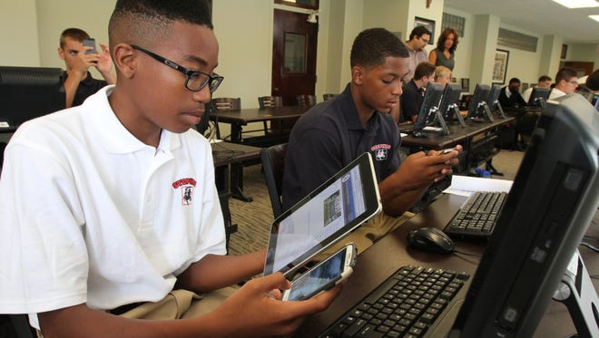 "Izayah Powell, left, and DeVante Reid set  up their  digital devices during freshman orientation at Archbishop Stepinac High School in White Plains, N.Y., on Sept. 5, 2013. The school is dropping all textbooks in favor of a ""digital library."""