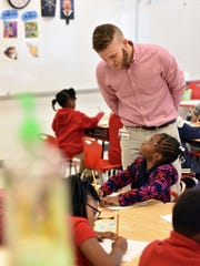 Elementary school teacher Matt Gandy interacts with his students as they practice writing at Casey Elementary School in Jackson.