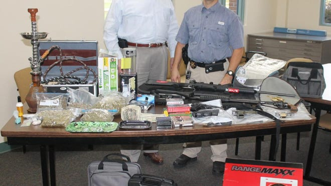Jefferson County Sheriff Gary Hutchins (at left) and Lt. William Schmidt (at right) stand with the items seized during a search of the house where Dwight Martell Poitier was living.