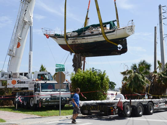 Work crews lift a 37-foot sailboat named Mistress onto