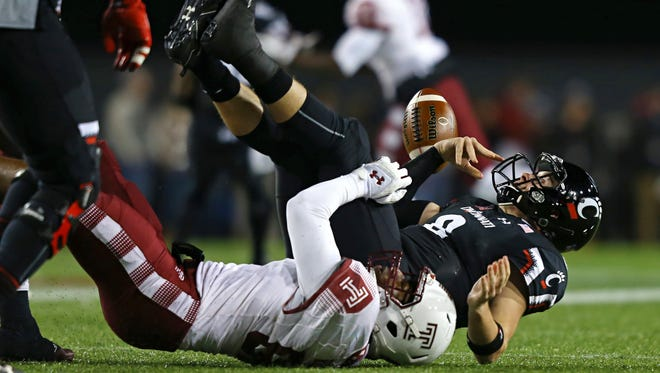 Cincinnati Bearcats quarterback Hayden Moore (8) fumbles as he is tackled by Temple Owls defensive lineman Quincy Roche (90) in the first half at Nippert Stadium.