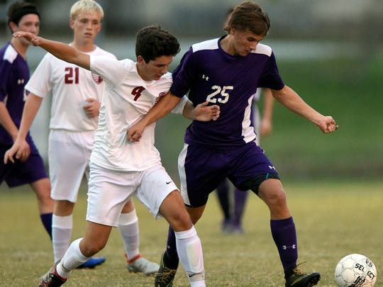 Henderson Countys Patrick Cloutier battles with Max Wadlington of Lyon County during the first half of the the Boys Second Region Soccer Tournament at Donley Field in Madisonville Tuesday.  Henderson won 6-1.