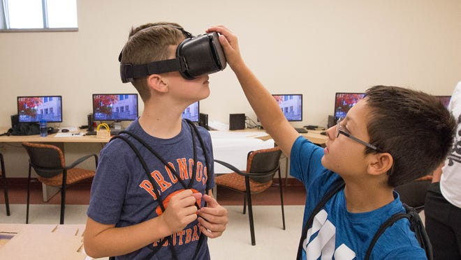 Joshua Campion,11, left, gets some help with a Virtual Reality headset from Andrew Vanlandingham, 11, during the Verizon Innovation Learning - Minority Males Program at New Mexico State Univeristy, Tuesday July 24, 2018.