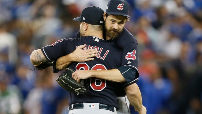 Oct 17, 2016; Toronto, Ontario, CAN; Cleveland Indians relief pitcher Andrew Miller (facing) hugs first baseman Mike Napoli (26) after game three of the 2016 ALCS playoff baseball series against the Toronto Blue Jays at Rogers Centre. Mandatory Credit: John E. Sokolowski-USA TODAY Sports