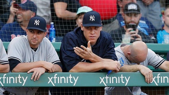 New York Yankees' Aaron Judge, center, watches from the dugout during the ninth inning of a baseball game against the Boston Red Sox in Boston, Saturday, Aug. 4, 2018.