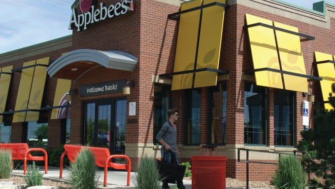 A Food Dudes driver leaves Applebee's on East 10th Street with an order.