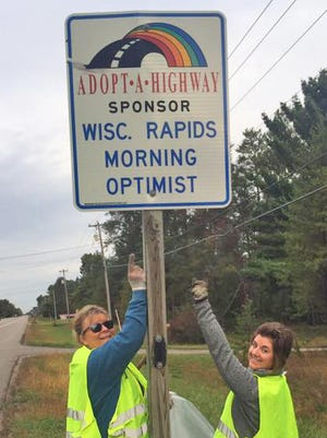 Optimist members Debra Jaborek and Raquel Nowak clean up a stretch of road on Highway 73 in October 2017.