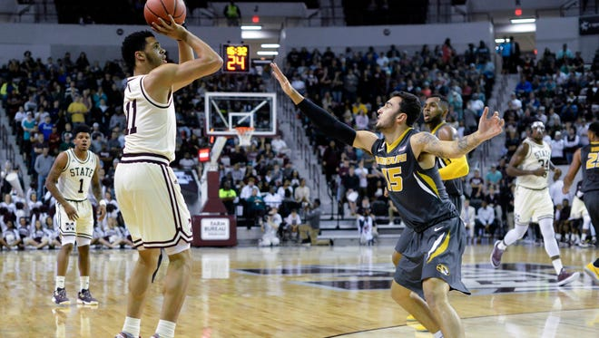 Mississippi State's Quinndary Weatherspoon (11) shoots as he is defended by Missouri Tigers guard Jordan Geist (15).