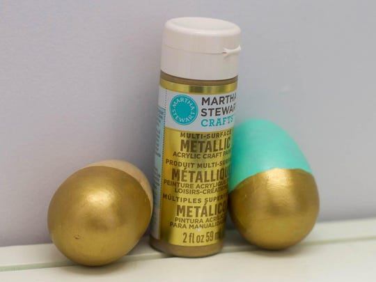 Two wooden Easter eggs are decorated using acrylic paint. This was the most inexpensive of the three tested techniques but required multiple coats of paint to achieve opaque coverage.