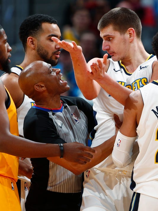 Referee Tre Maddox, left, controls Denver Nuggets center Nikola Jokic, of Serbia, after he was assessed a flagrant foul against Utah Jazz forward Jonas Jerebko in the second half of an NBA basketball game Tuesday, Dec. 26, 2017, in Denver. Jokic was ejected from the game. The Nuggets won 107-83. (AP Photo/David Zalubowski)