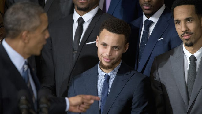 President Barack Obama points to Golden State Warrior basketball player Stephen Curry, center,  during a ceremony in the East Room of the White House in Washington, Thursday, Feb. 4, 2016, where the president honored the 2015 NBA Champions.