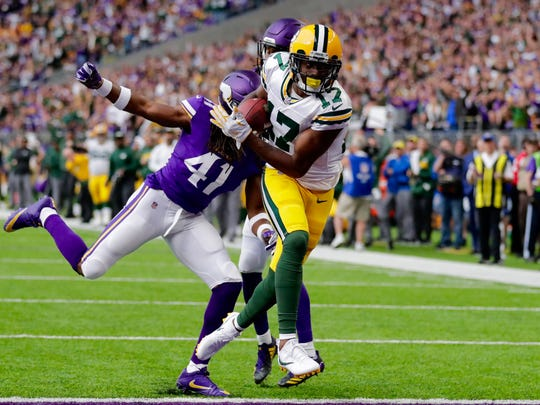 Davante Adams reaches the end zone with Minnesota's Anthony Harris in pursuit to finish off a touchdown reception from Brett Hundley in the second quarter of Sunday's game at U.S. Bank Stadium in Minneapolis.