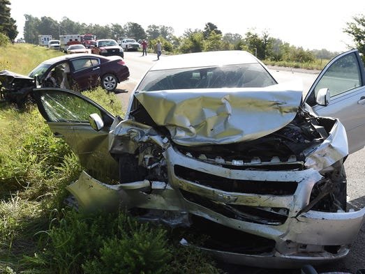 Emergency personnel work the scene of a three-vehicle accident Monday, Aug. 25, 2014, one mile east of the Baxter/Fulton county line on U.S. Highway 62. Two people were airlifted from the scene with injuries.