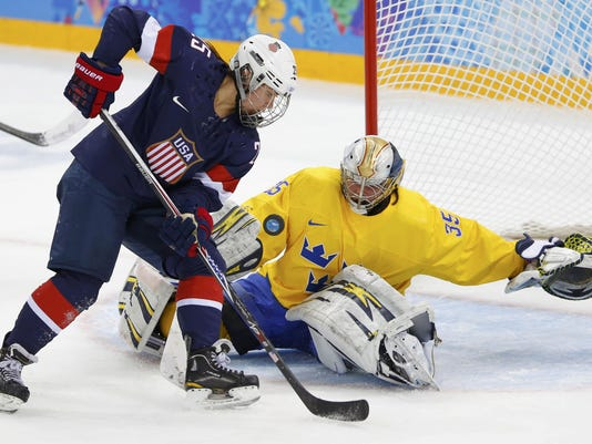 Team USA's Schleper drives to the net on Sweden's goalie Wallner during the second period of their women's ice hockey semi-final game at the Sochi 2014 Winter Olympic Games