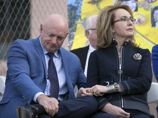 Former Arizona congresswoman Gabrielle Giffords holds the hand of her husband, Mark Kelly, during the memorial dedication for Tucson's January 8th Memorial at El Presidio Park in Tucson. The dedication marked the seventh anniversary of a  mass shooting that left six people dead and 13 others injured, including Giffords.