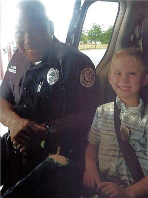 Clarksville Police Officer Evon Parkes, left, with Junior Officer Quintin Fisher, 8.