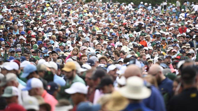 Patrons crowd the open area near the green jacket presentation after the final round of the 2019  Masters Tournament at Augusta National Golf Club. The 2020 tournament in November will be held patron-free.