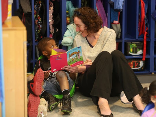 Jean Hurst, a visiting teacher from Genesee Community Charter School, reads with kindergarten student Anthony McMillan at School 8. The two schools are collaborating on the K-2nd-grade curriculum.