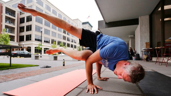 Matt Pierce performs the yoga position side crow during Spark Lafayette-West Lafayette Tuesday, July 11, 2017, at Chase Plaza in downtown Lafayette. Spark Lafayette-West Lafayette is a program of free activities for people to enjoy and participate in both Lafayette and West Lafayette. Other activities include chess, dancing, ping pong, music and more. Pierce grew up in Lafayette, but now calls Seattle home. He is visiting the area.
