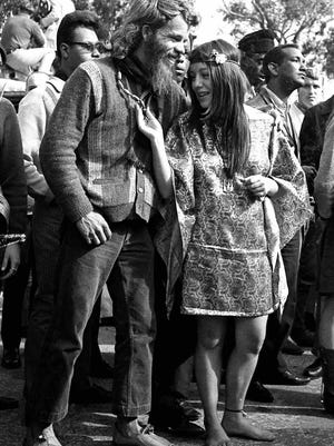 "Will investors profit in a ""Summer of Love,""  Wall-Street style. A young barefoot woman examines a friend's necklace during a festival in San Francisco's Golden Gate Park on Aug. 8, 1967, during what became known as the Summer of Love. (AP Photo/file)"