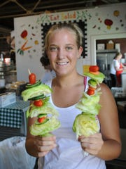 Taylor Ginn, 17, of Des Moines, holds onto a couple salad on a stick food items in the agricultural building at the 2008 Iowa State Fair Saturday, Aug. 9.