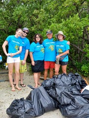 A team of volunteers from LW Marketing proudly displays the bags of garbage they collected from Dog Beach during Coastal Cleanup 2014.