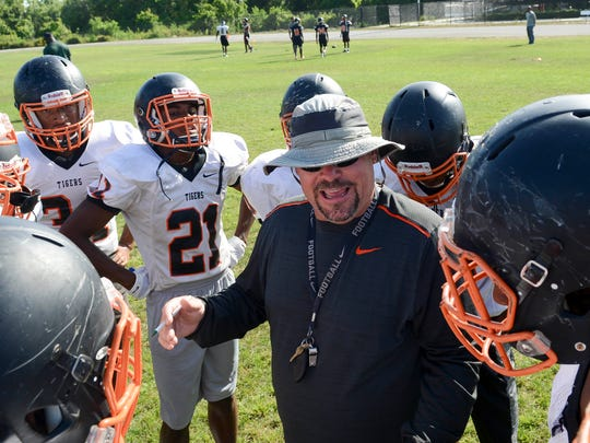 Cocoa head football coach John Wilkinson talks with his players during practice at Cocoa High School