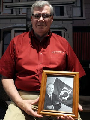"""Irondequoit resident Rick Collins with a photo of his """"Uncle Newt,"""" who created the famous image seen on the POW/MIA flag."""