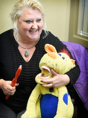 Public Health Dental Hygienist Practitioner Joy Brown-Walb demonstrates how to properly brush your teeth on a puppet at Lebanon Ridge Oral Health on Nov. 15 2017.