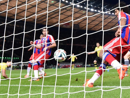 In this picture taken Saturday May 17, 2014, Bayern's Dante kicks the ball during the German soccer cup final between Bayern Munich and Borussia Dortmund in Berlin.  Referee Florian Meyer has defended his decision not to award Borussia Dortmund a goal in Saturday's German Cup final despite replays suggesting the ball crossed the line. Mats Hummels' header was cleared on or behind the line by Bayern Munich defender Dante in the 64th minute with the game still scoreless. It wasn't awarded and Bayern went on to win 2-0 in extra time. (AP Photo/dpa, Maurizio Gambarini)