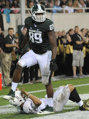 MSU's Shilique Calhoun walks away after leveling Western Michigan quarterback Zach Terrell on Aug. 30, 2013, at Spartan Stadium in East Lansing. Calhoun recovered a fumble for a touchdown and had three QB hits as the Spartans defeated the Broncos, 26-13.